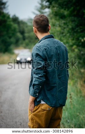 Young man standing on the road, looking in the car coming towards him. Vintage Instagram style effect, soft and selective focus, shallow DOF, low light, grain texture visible on maximum size - stock photo