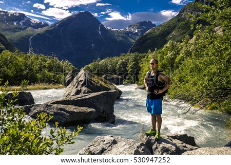 Young man standing on the stone next to the river, Norway