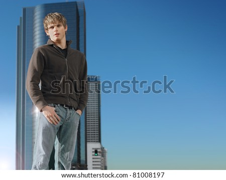 Young man standing outdoors against background of empty blue sky and modern building