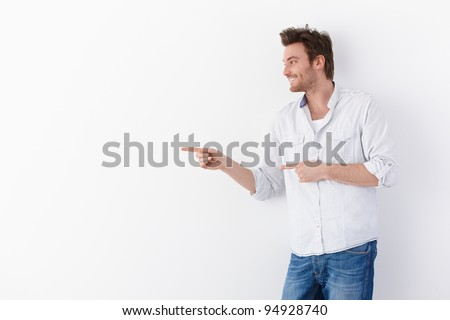 Young man standing over white background, pointing to right, smiling.? - stock photo