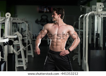 Young Man Standing Strong In The Gym And Flexing Muscles - Muscular Athletic Bodybuilder Fitness Model Posing After Exercises