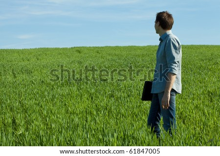 young man standing with a laptop in the green field - stock photo