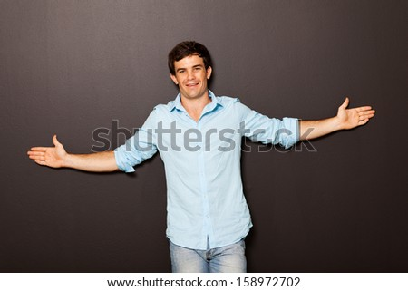 young man standing with arms open - stock photo