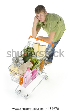 Young man standing with full of things trolley. Looking sad and exhausted. Whole body. Isolated on white in studio. looking at camera