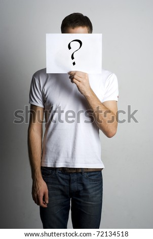 Young man standing with question mark on board - stock photo