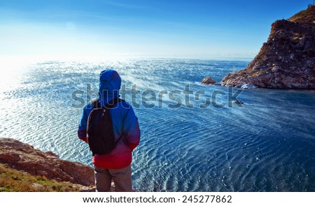 young man stands on a hill on a background of the sea - stock photo