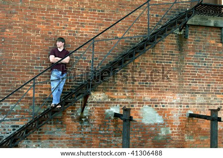 Young man stands on metal fire escape propped against an aging brick wall in an alley in Alabama. - stock photo
