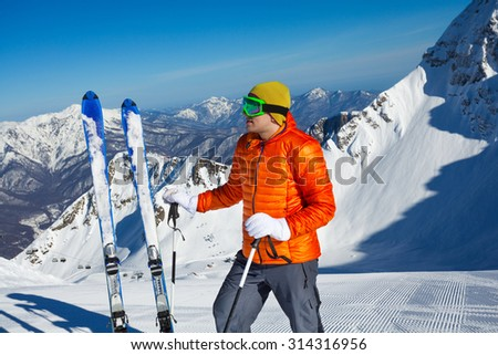 Young man stands with ski in snow and beautiful mountain view on background in sunny weather on Krasnaya polyana, Sochi - stock photo