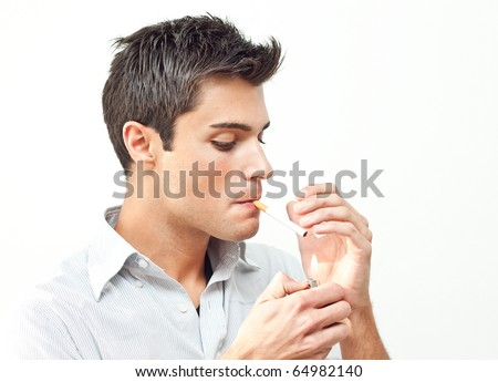 Young man starting smoking a cigarette - stock photo