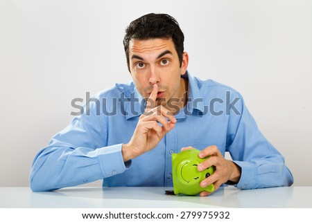 Young man stealing money from piggy bank - stock photo