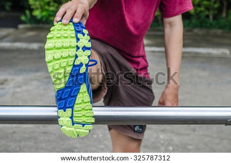 Young man stretching her legs outdoors in the park - stock photo