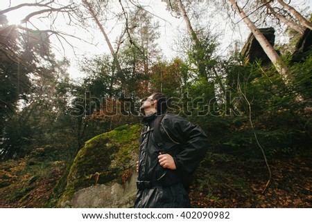 Young Man,Student hiking in forest.Man hiker smiling happy portrait looking up enjoying nature during a trekking trip. Side view of a young man outdoors in nature on a hiker path in forest. - stock photo