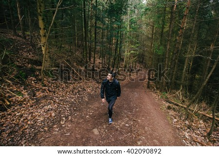 Young Man,Student hiking in forest.Man hiker smiling happy portrait looking up enjoying nature on foggy day during a trekking trip. Back of a young man outdoors in nature on a hiker path in forest. - stock photo
