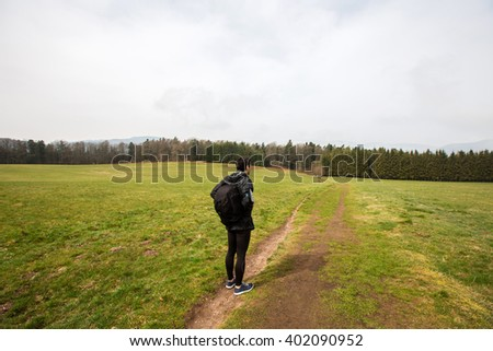 Young Man,Student hiking in forest.Man hiker smiling happy portrait on foggy day during a trekking trip. Back of a young man outdoors in nature on a hiker path in forest. - stock photo