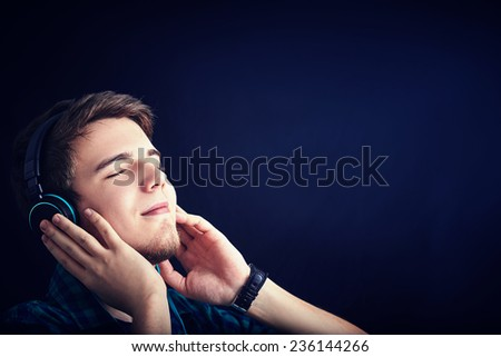 Young man student  listening  to music with pleasure isolated on black background. - stock photo