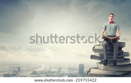 Young man student sitting with book in hands - stock photo
