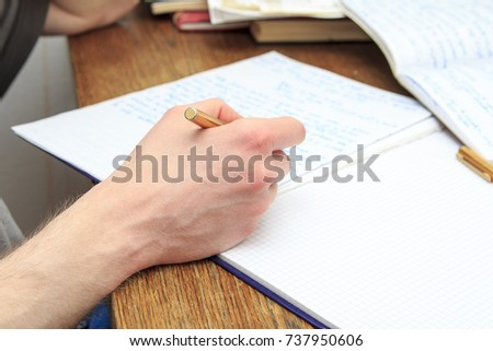 Young man studying, writing down notes in a notebook