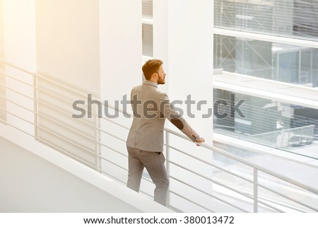 Young man successful engineer looking through window on a new building construction of which he developed, male entrepreneur in suit thinking about important forthcoming meeting with investors - stock photo