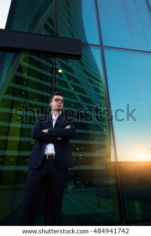 Young man successful lawyer dressed in luxury expensive clothes is waiting outdoors his client before beginning trial. Handsome male economist is standing outside office building after hard work day