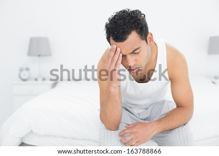Young man suffering from headache in bed at home