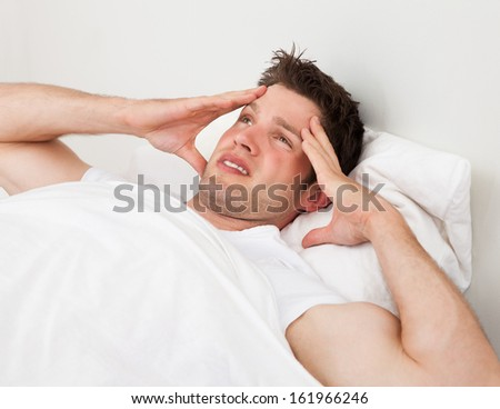 Young Man Suffering From Headache Lying On Bed
