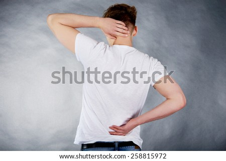 Young man suffering from neck pain. - stock photo