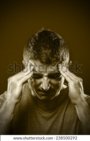 young man suffering migraine and headache in intense pain feeling desperate and sick with hands on tempo isolated on grunge studio background - stock photo