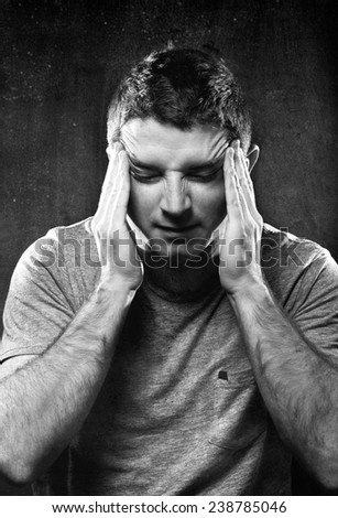 young man suffering migraine and headache in intense pain feeling desperate and sick with hands on tempo in stress isolated on studio background black and white - stock photo