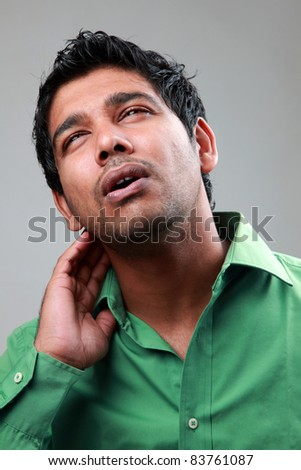Young man suffers from neck pain - stock photo