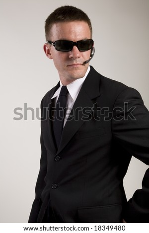 Young man suggesting a secret service agent or secret policeman being watchful and observant. - stock photo