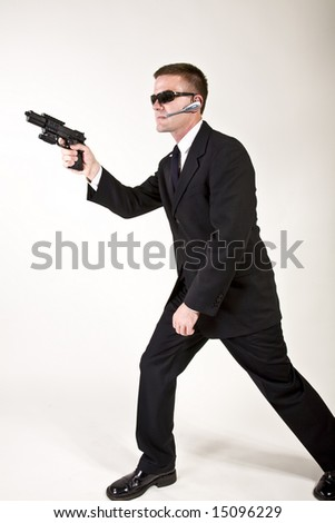 Young man suggesting a secret service agent or secret policeman pointing a gun. - stock photo