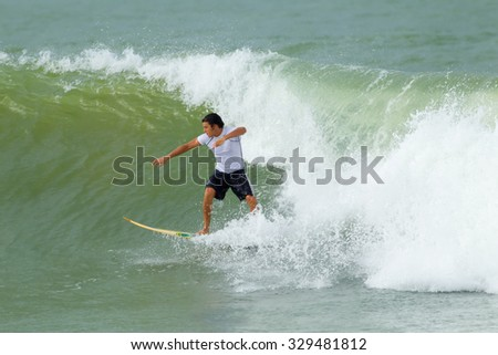 Young Man Surfing On A Balsa Surfboard - stock photo