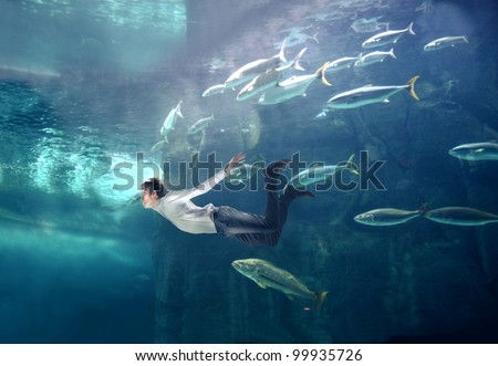 Young man swimming in a fish tank - stock photo