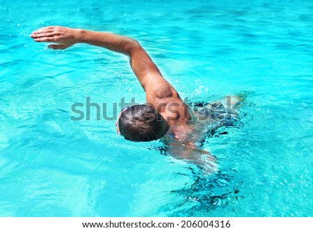Young man swimming  in a pool - stock photo