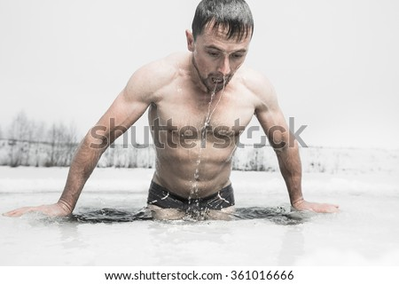 Young man swimming in the ice hole - stock photo