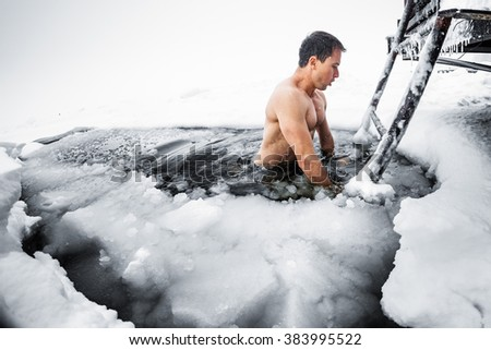Young man swimming in the ice hole on a winter lake - stock photo