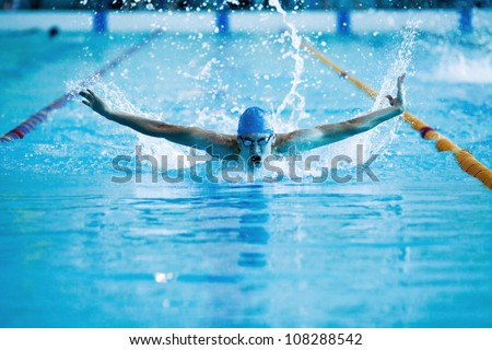 young man swims the butterfly in the pool - stock photo