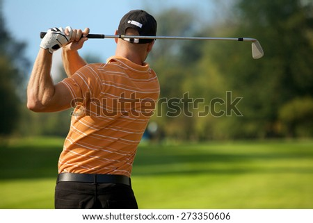 Young man swinging golf club, rear view - stock photo