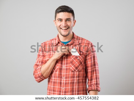 Young man takes out blank business card from the pocket of his shirt isolated on gray background - stock photo