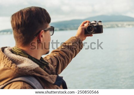 Young man takes photographs self-portrait with old photo camera on coastline on background of sea. Focus on camera - stock photo