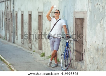 Young man taking a photo with his smart phone while standing on the city street with his bicycle beside him