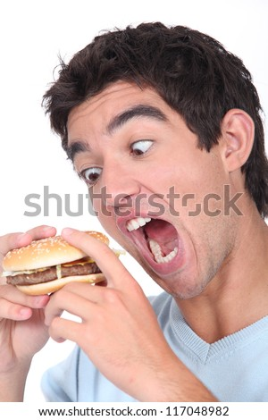 Young man taking an exaggerated bite out of a hamburger - stock photo
