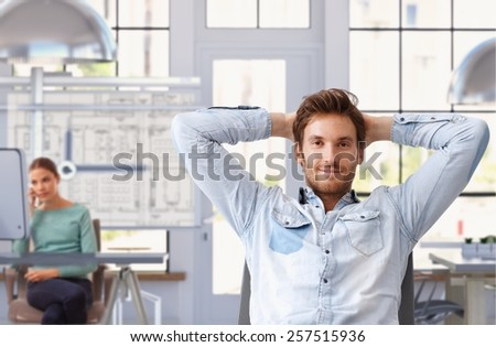 Young man taking break of work at trendy architect office - stock photo