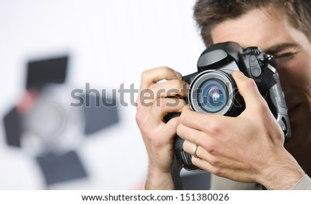 Young man taking photo with professional digital camera