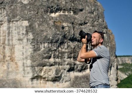 Young man taking pictures in the mountains