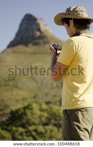Young man taking pictures on a hiking trip