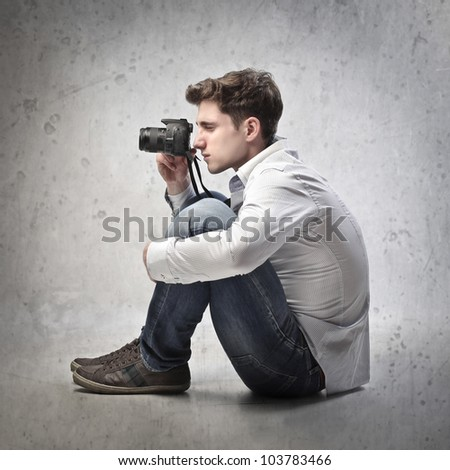 Young man taking pictures with a camera - stock photo