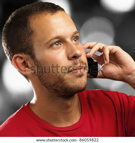 young man talking on mobile phone against a city background - stock photo