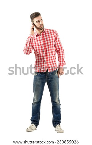 Young man talking on mobile phone looking away. Full body length portrait isolated over white background.  - stock photo