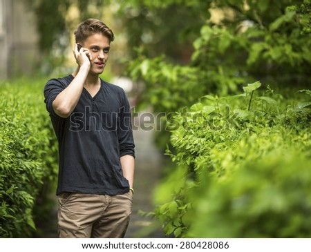 Young man talking on mobile phone outdoors. - stock photo
